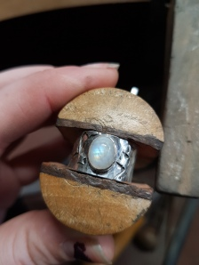 Rainbow moonstone, sterling silver ring with a wide hammered band and little ivy leaves either side of the stone. Designed based on a clients daughters love for plants especially ivy.